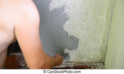 Man plastering with a spatula wall - The man plastering with...
