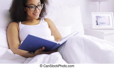 african woman reading book in bed at home bedroom