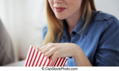 happy woman eating popcorn and watching tv at home