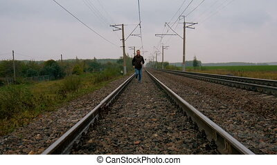 Man runs on railroad tracks. - Man runs on railroad tracks...