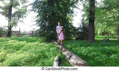 Teen boy and girl child walking on a log. Brother and sister...