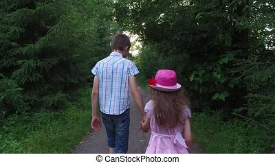 Teen boy and girl child are on track in the park. Brother and sister holding each other's hands. Old overgrown park.