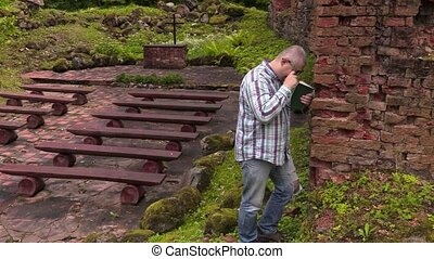Man cries at the wall in old outdoor church