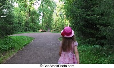 Girl child goes on an asphalt track. The path follows the old park. Summer sunny evening. Perfect weather for a walk.
