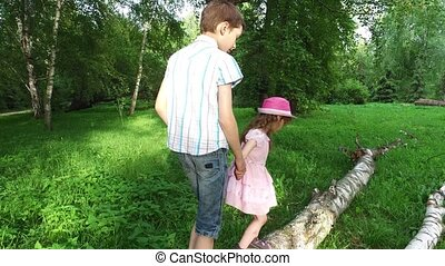 Teen boy and girl child walking on a log. Brother and sister helping each other to walk on the balance beam.