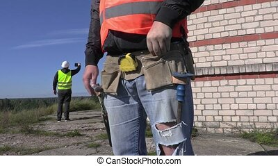 Construction worker try to find nails in to builders tool...
