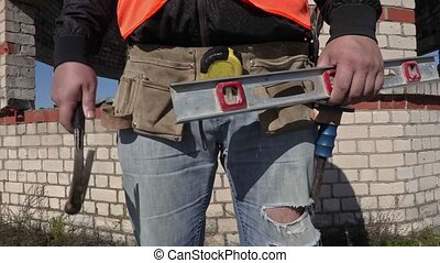 Construction worker put hammer in to builders tool belt