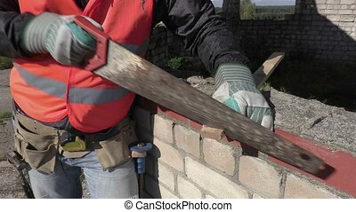 Construction worker using handsaw