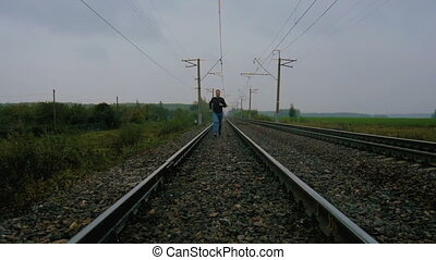 Man runs to the meeting, on railroad tracks, slow motion