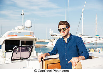 Bearded man wearing sunglasses and standing on a yacht -...