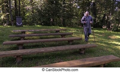 Tired hiker with walking sticks on bench in park