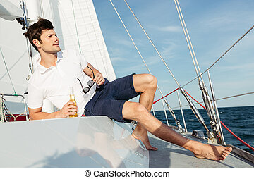 Handsome young man drinking beer while resting on the yacht...