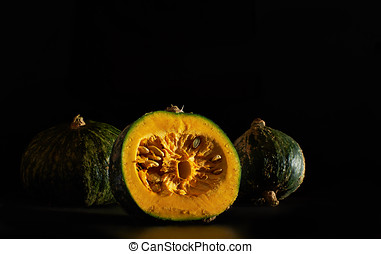 Kabocha pumpkins over a black background. - Kabocha squash,...