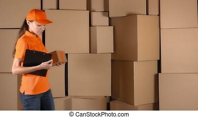 Female courier in orange uniform delivering a parcel to...