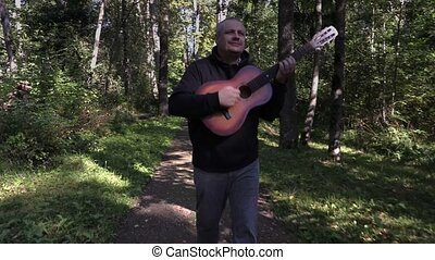 Happy man playing guitar and walking in park