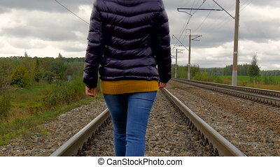 Woman walking on railroad tracks.