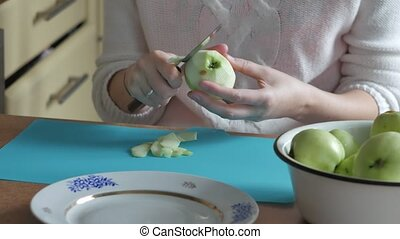 A woman peeled an apple on a plate. Part 1. Woman clears the...
