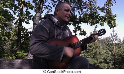 Man playing guitar in wooden tower near trees