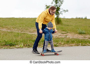 happy father and little son on skateboard - family,...