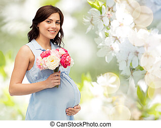happy pregnant woman with flowers touching belly -...