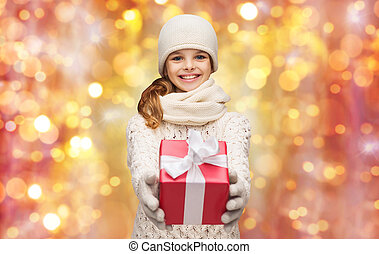 happy girl in hat, scarf and gloves with gift box
