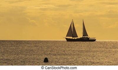 sailing ship passing by - sailing ship on horizon at sunset