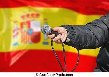 Hand holding microphone in spanish survey - Presidential...