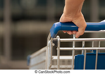 Woman driving shopping cart in front of the supermarket