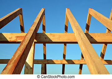 Wooden Roof frame rafters against a blue sky.