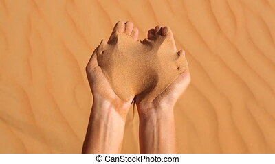 sand running through fingers of han