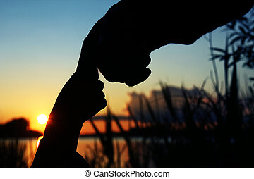 silhouette of hands of parent and child at sunset