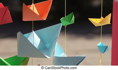 Paper boats on stretched ropes - Colored paper boats hanging...