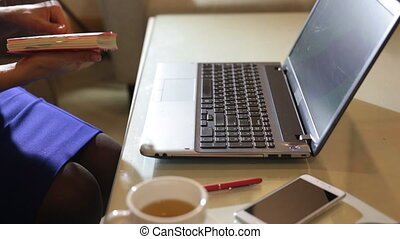 beautiful young woman is seating indoors at a cafe restaurant, holding a coffee cup while using her laptop pc