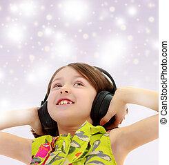 Little girl listening to music headphones. - Blue Christmas...