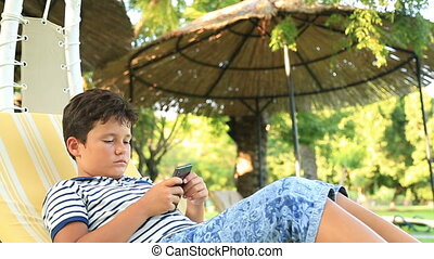 Child sitting on hammock with smartphone - Young boy using...