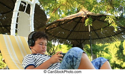 Child on hammock with smartphone - Young boy using mobil...