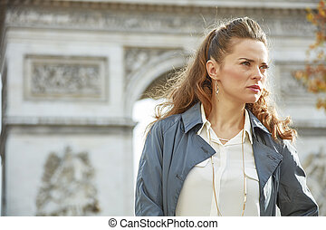 trendy woman in trench coat in Paris, France looking aside -...