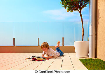 young boy, kid reading book on rooftop terrace, while lying...