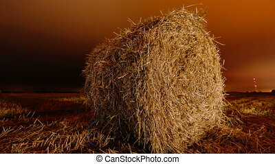 Roll of hay close-up night time lapse video
