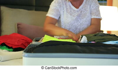 Woman packing suitcase in the bedroom