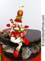 Funny snowman sits on vintage brouwn coffer with white...