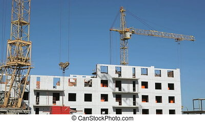Construction crane supplying slabs for builders - The...