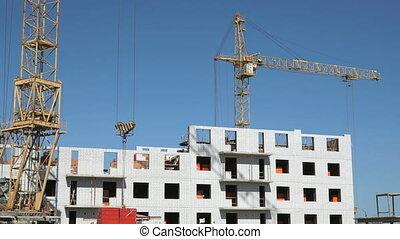 Construction crane supplying slabs for builders