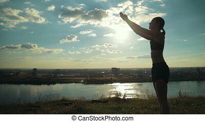 Woman practicing yoga in the park at sunset
