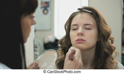 Beautiful bride gets a professional makeup done by the...