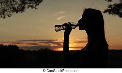 Silhouette of young woman drinking water