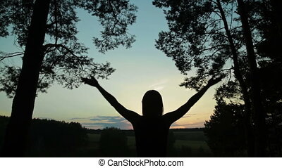 Happy young woman silhouette against sky lifts hands up in...