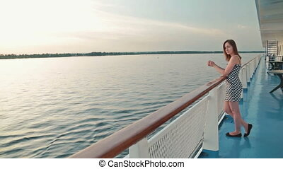 Young woman stands on deck of cruise ship