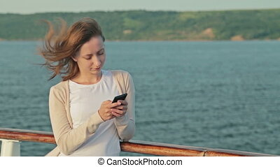 Woman using mobile phone on deck of cruise ship