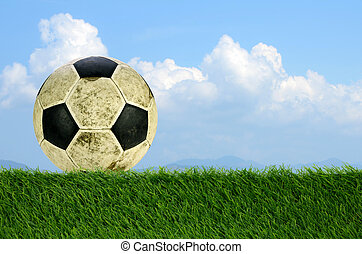 Shabby soccer ball on artificial turf field.